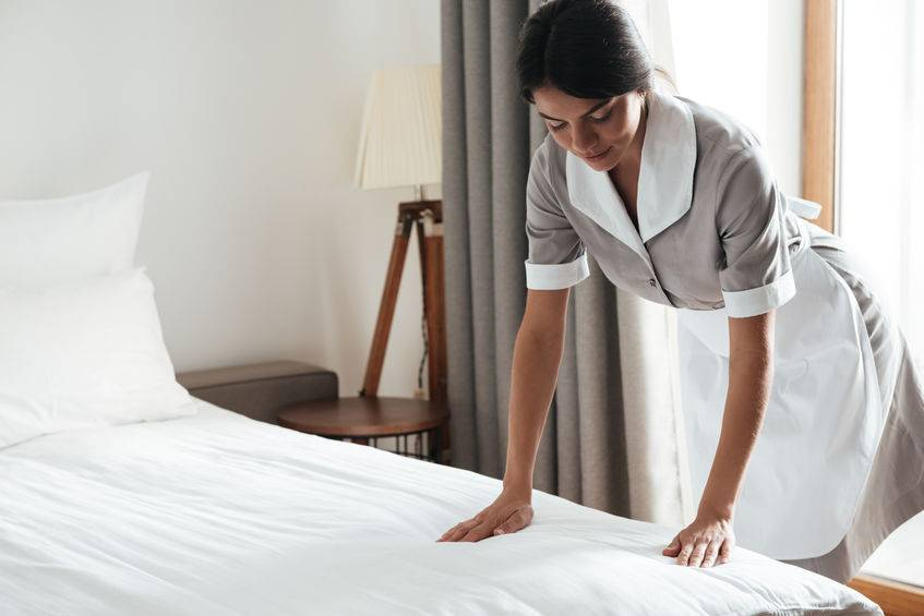 Maid setting up white bed sheet